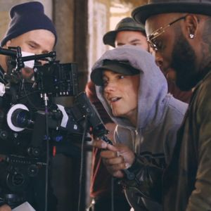 Eminem posing a smile in front of the camera on a video shoot